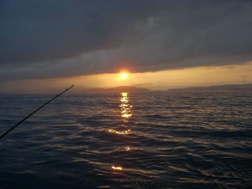 The sun rises over the Oregon Coastal Range off Depoe Bay.